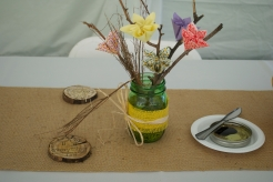 The centerpieces featured orgami flowers, baby breaths and twigs in mason jars